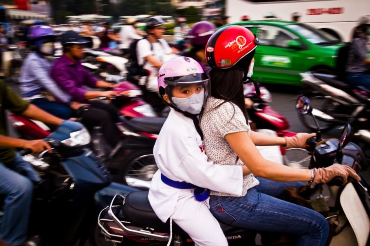 A young girl wearing a helmet in rush hour traffic in Saigon, Vietnam.