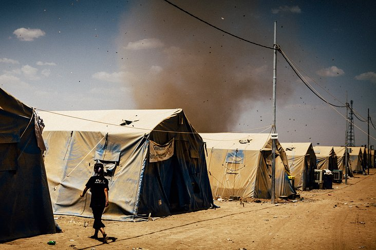 arising sandstorm in a refugee camp