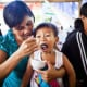 A child being fed at a nutrition support group meeting sponsored by UNICEF